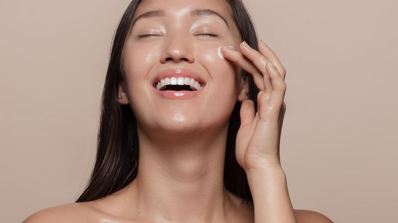 A woman applies face cream