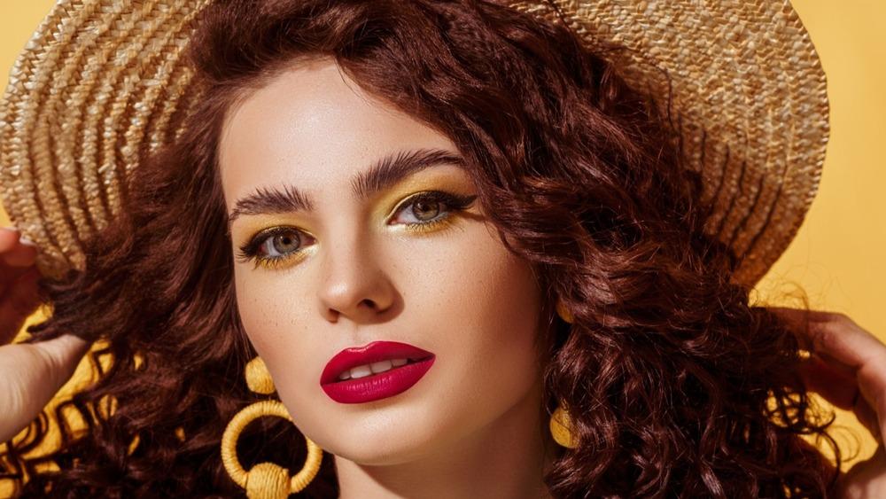 Woman putting bold and beautiful eyebrows on display