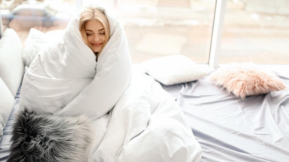 Woman snuggling in white duvet