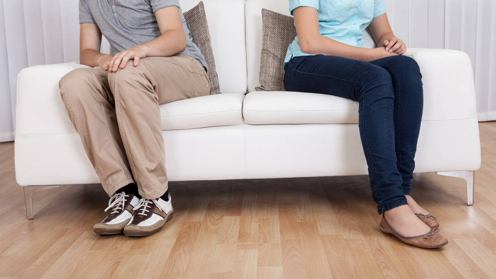 lower view of a couple distancing themselves on a couch