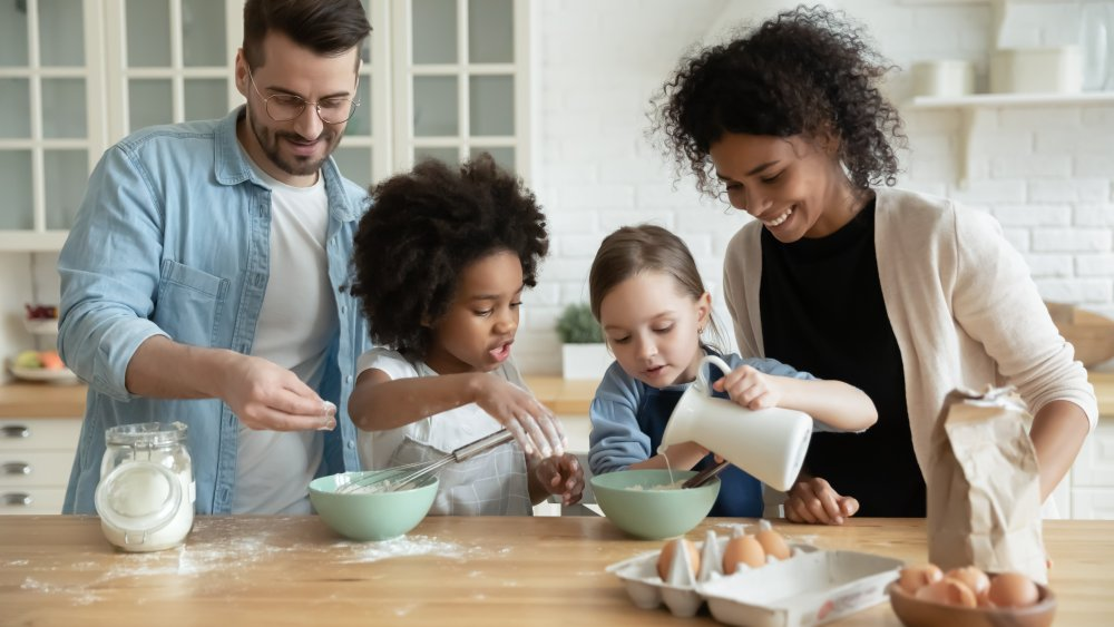 A family of four baking and pouring milk