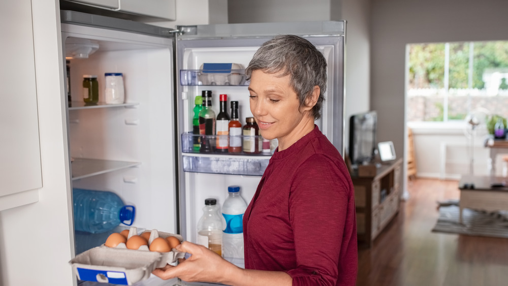 A woman smiling while removing eggs from the fridge