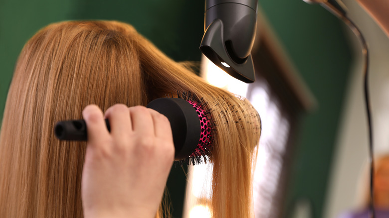 Stylist drying a redhead's hair in a salon using a round brush.