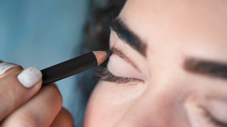 Woman having eye make-up applied