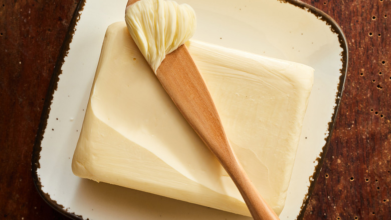 A slab of butter with a wooden spreader