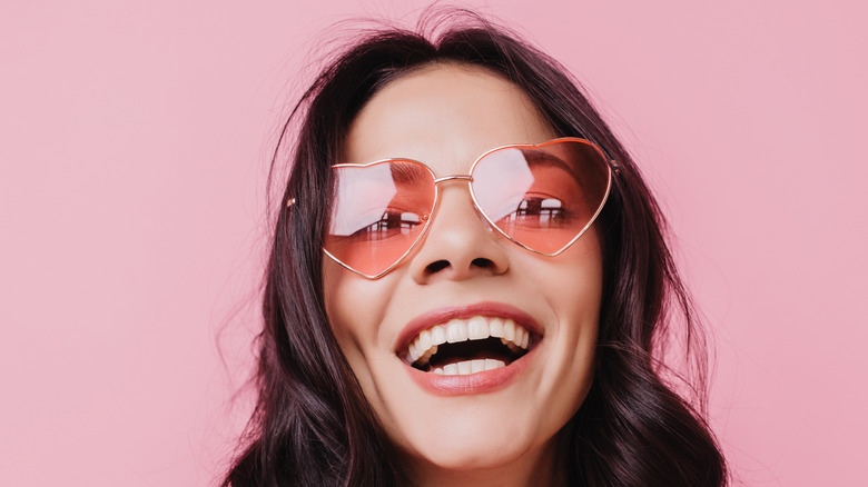 Woman smiling with heart-shaped sunglasses