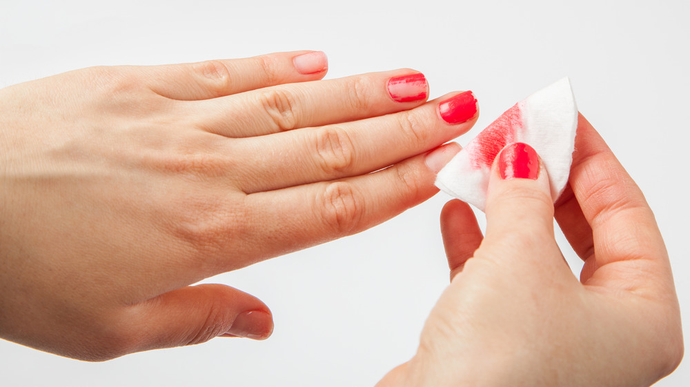 Person taking off red nail polish