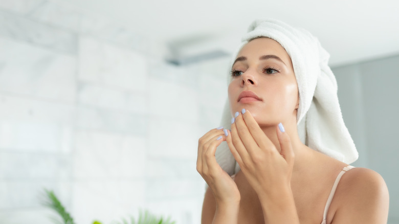 Woman applying serum to skin