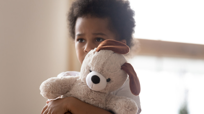 sad little girl holding stuffed animal