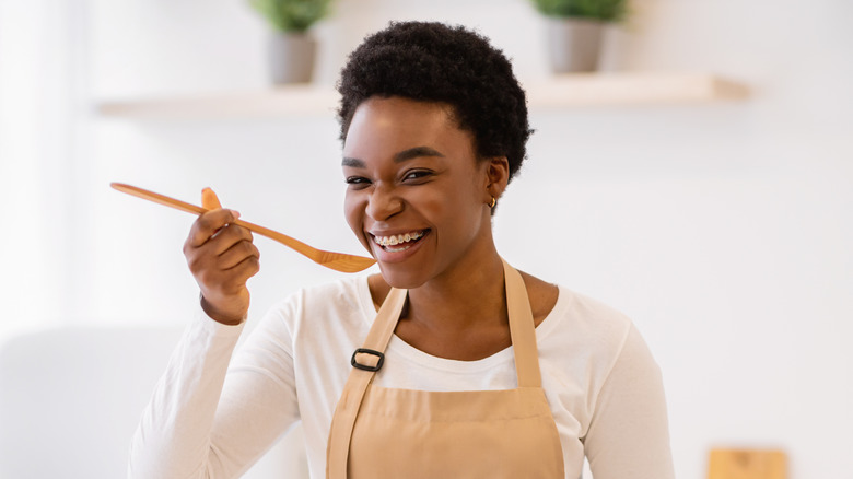woman tasting from spoon