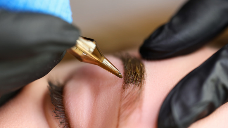 Microblading tool against woman's eyebrow