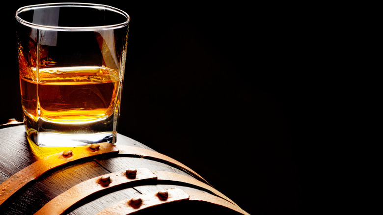 Glass of whiskey on top of a barrel