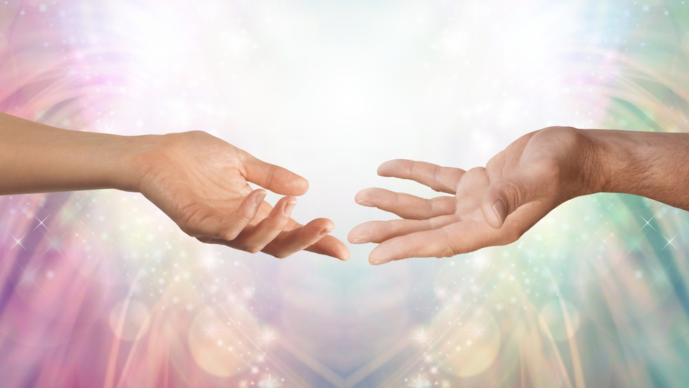 A masculine and feminine hand reaching toward each other