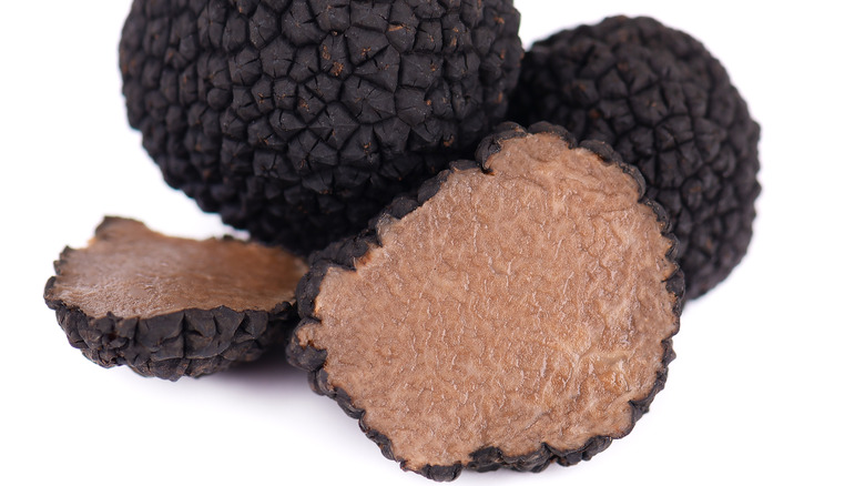 Whole and sliced black truffles