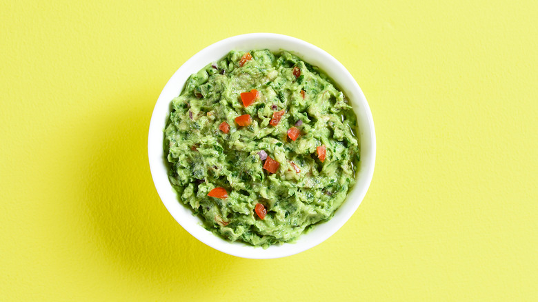 a bowl of guacamole with a lime green background