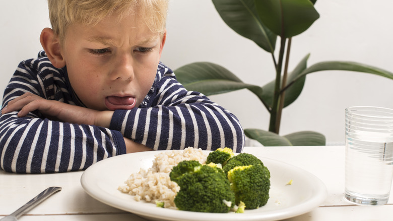 Child making an angry face while looking at veggies