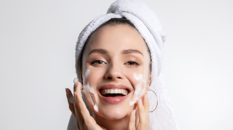 woman washing face and smiling