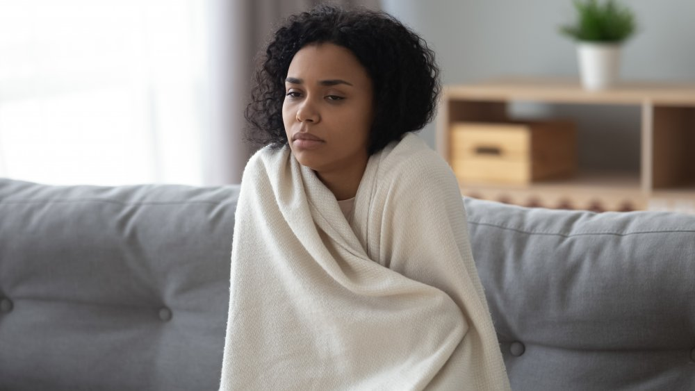A cold woman wrapped in a blanket