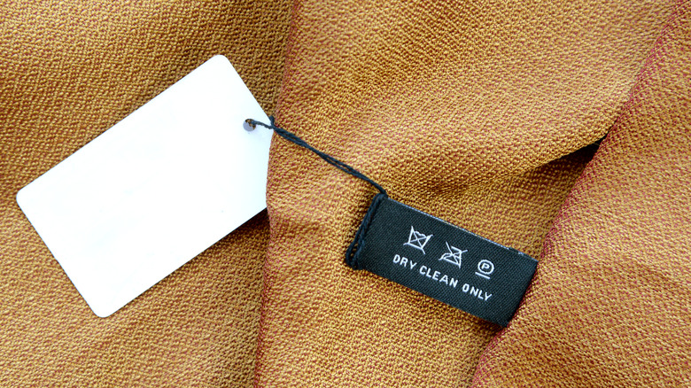 Clothing label on woven gold and red silk fabric