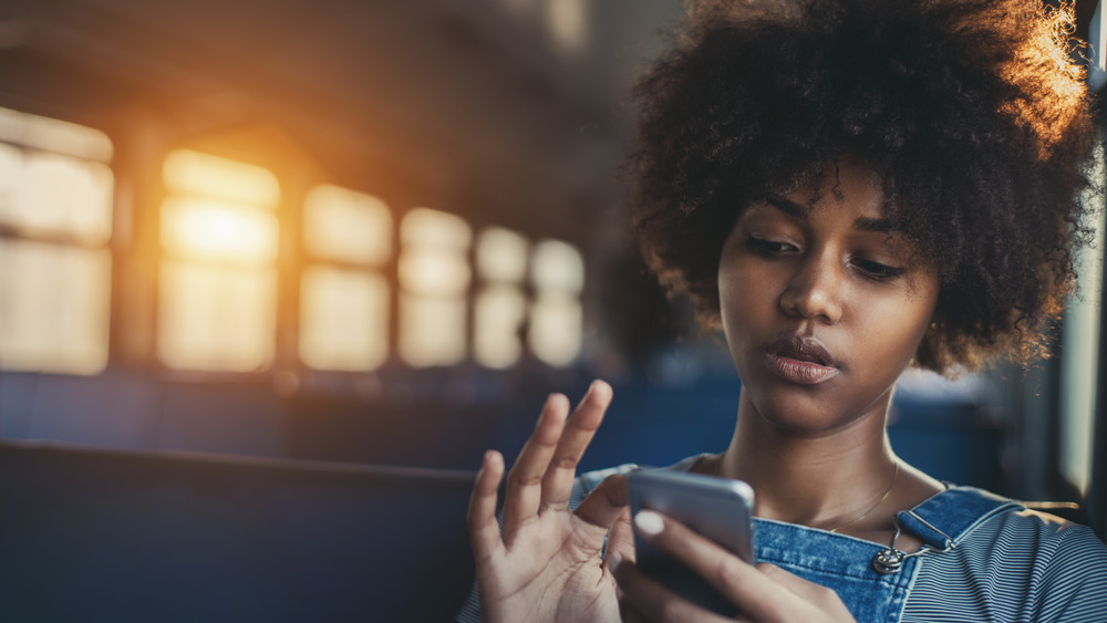 Young woman sitting on the bus using her phone