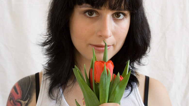 Woman with tattoos holding a red tulip