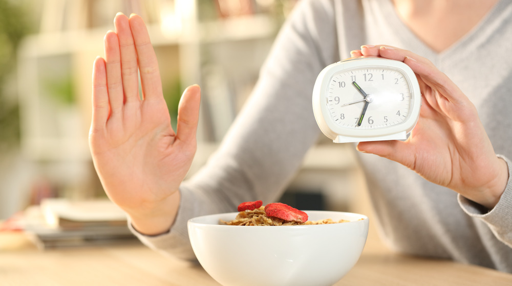 Woman holding an alarm clock with her hand out over a bowl of cereal.