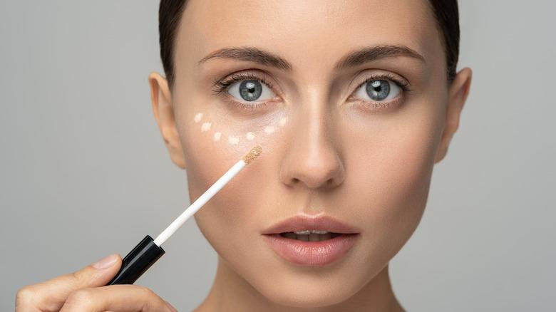 Woman applying concealer under her eyes