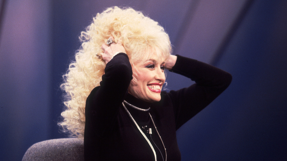 Dolly Parton holding wig