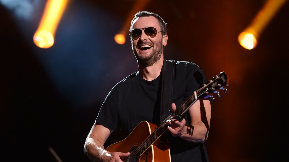 Eric Church smiling with guitar