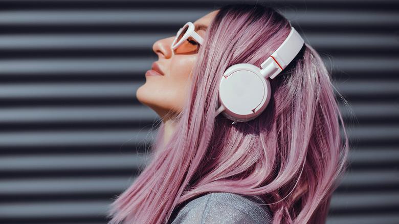 Pink-hair woman wearing white headphones