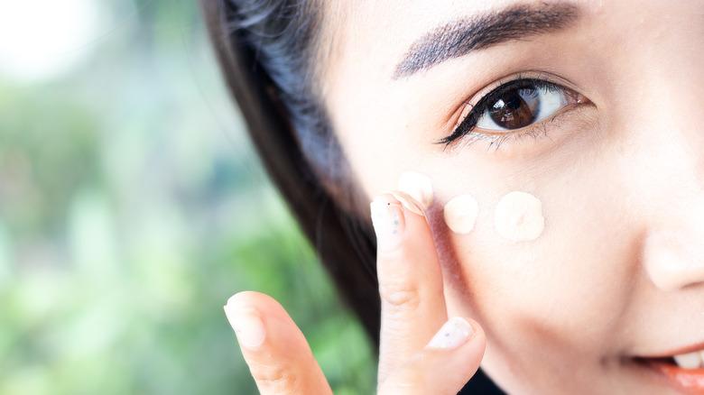 woman applying eye brightener