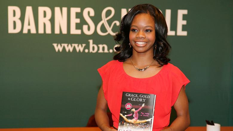 Gabby Douglas holding her autobiography