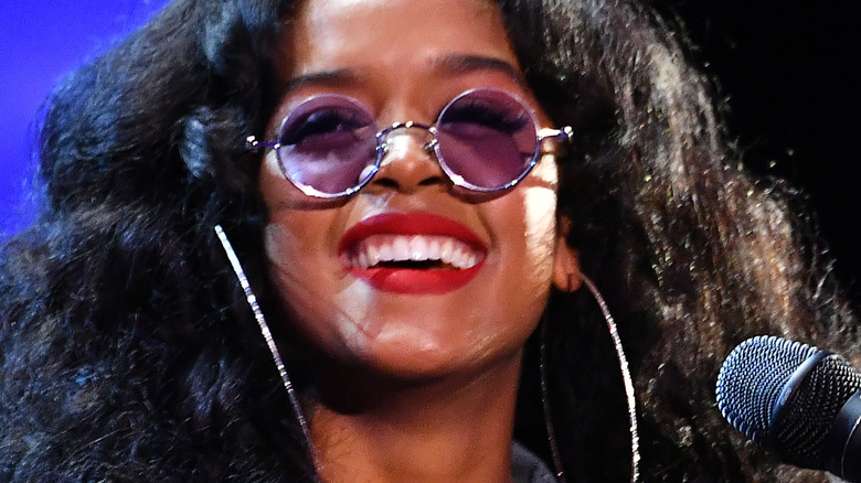 H.E.R. smiling on stage