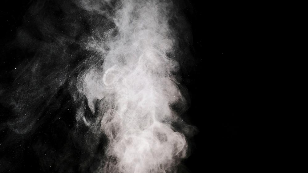 smoke puffing upwards with a black background