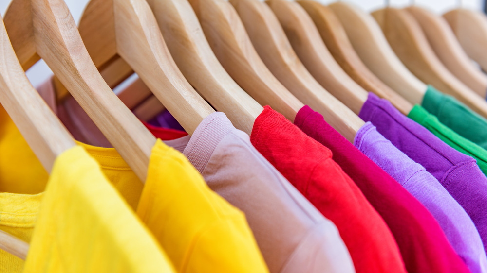 Colorful shirts hanging in a closet