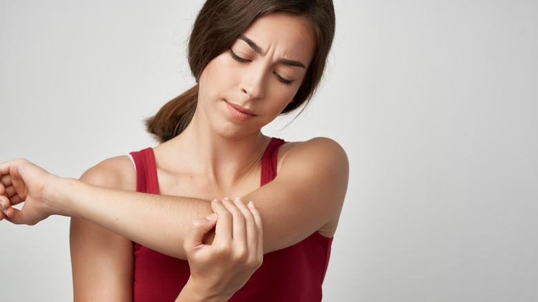 concerned woman looking at her arm