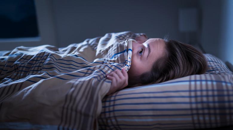 woman hiding bed