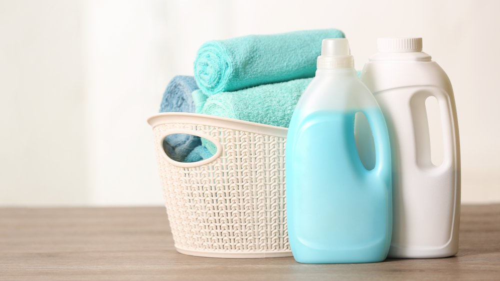 two bottles of laundry detergent and folded towels