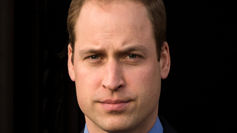 Prince William posing against a black background