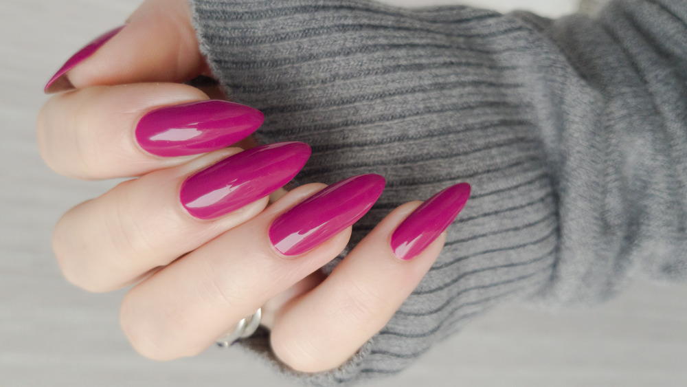Woman's hand with long pink nails