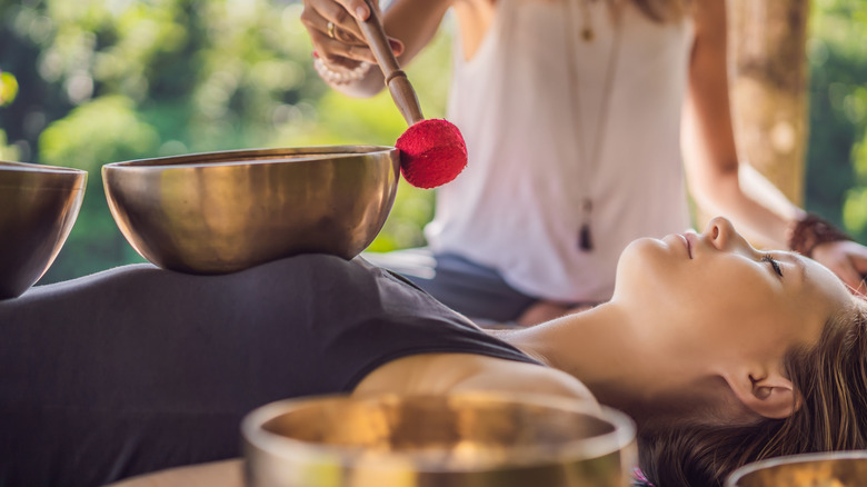 Woman playing a singing bowl on a person's body