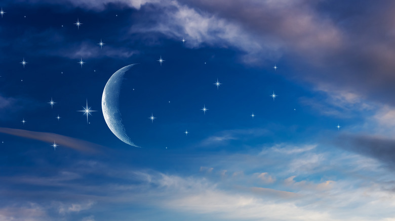 New moon and stars in sunset sky