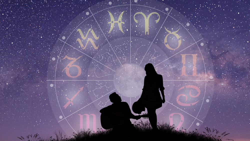 couple under a sky full of stars with zodiac signs