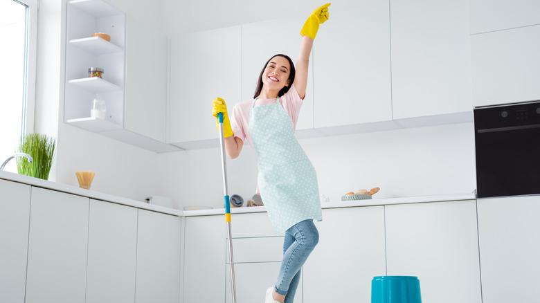 Happy woman cleaning kitchen floor
