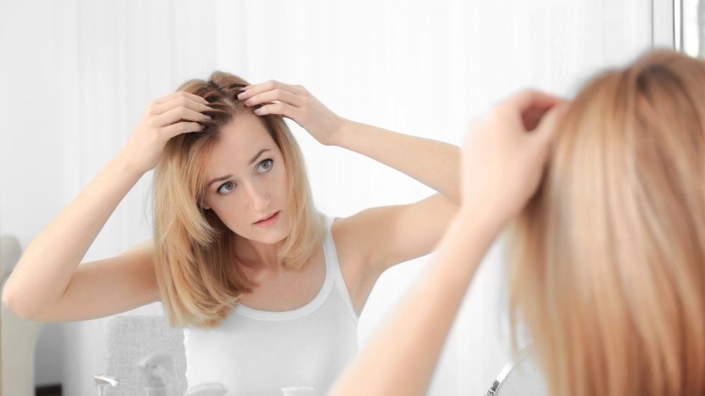 woman examining hairline
