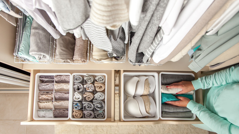 Bird's-eye view of closet drawers with well-organized clothing inside, neutral colors
