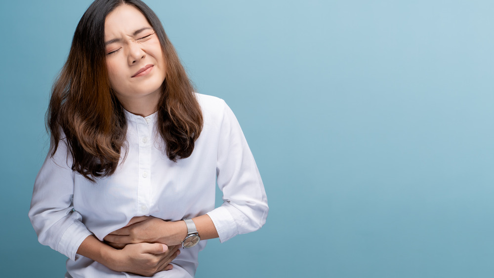 Woman with painful cramps clutching stomach