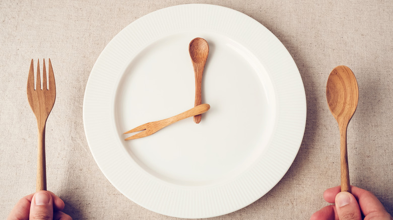 White plate with wooden fork and spoon arranged like a clock.