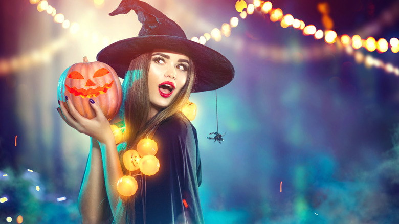 Woman dressed as a witch holding a pumpkin