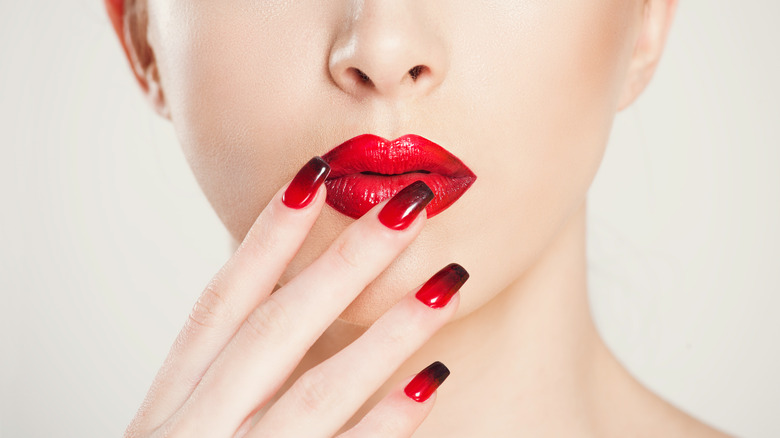 Woman holding dramatic square nails next to her red lips.